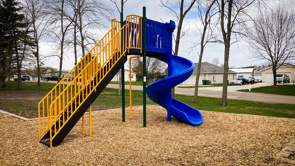 Blue slide with stairs and top platform. Playground company Cedar Rapids, Iowa playground installation playground equipment slides swings surfacing climbers children recreation safety durable