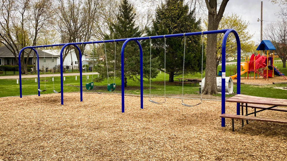 Swing set with blue metal frame for small residential park. Playground company Cedar Rapids, Iowa playground installation playground equipment slides swings surfacing climbers children recreation safety durable
